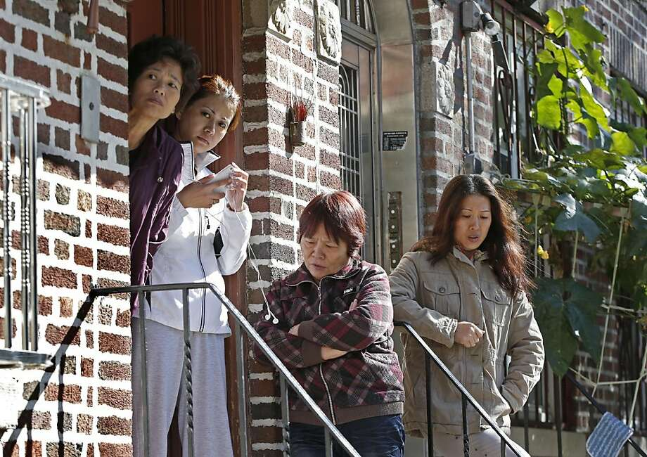 Neighbors gather on the steps of a building near the scene of a mass slaying in Sunset Park, a neighborhood in Brooklyn with a large Chinese community. Photo: Kathy Willens, Associated Press
