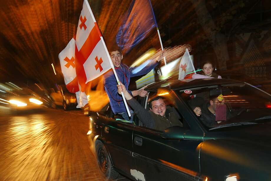 Georgians drive around Tbilisi with national flags to celebrate after the main independent exit poll indicated former university rector Giorgi Margvelashvili won about 67 percent of the vote. Photo: Sergei Grits, Associated Press