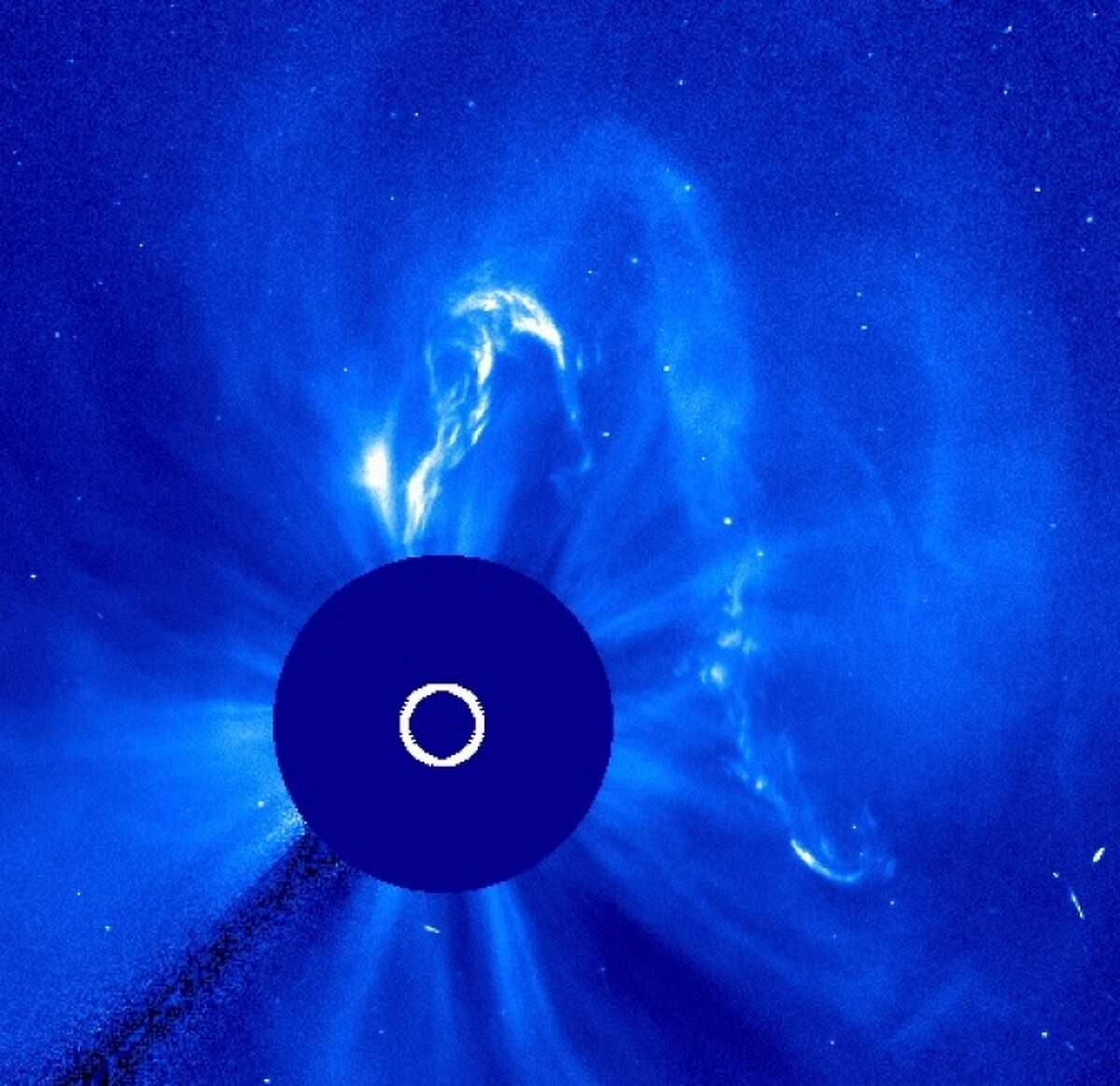 A coronal mass ejection shoots up from the sun in this image of the sun's atmosphere. The sun is obscured by the blue disk so that the dimmer atmosphere can be seen. This image was captured by the European Space Agency/NASA's Solar and Heliospheric Observatory at 9:54 p.m. EDT on Sept. 29, 2013.