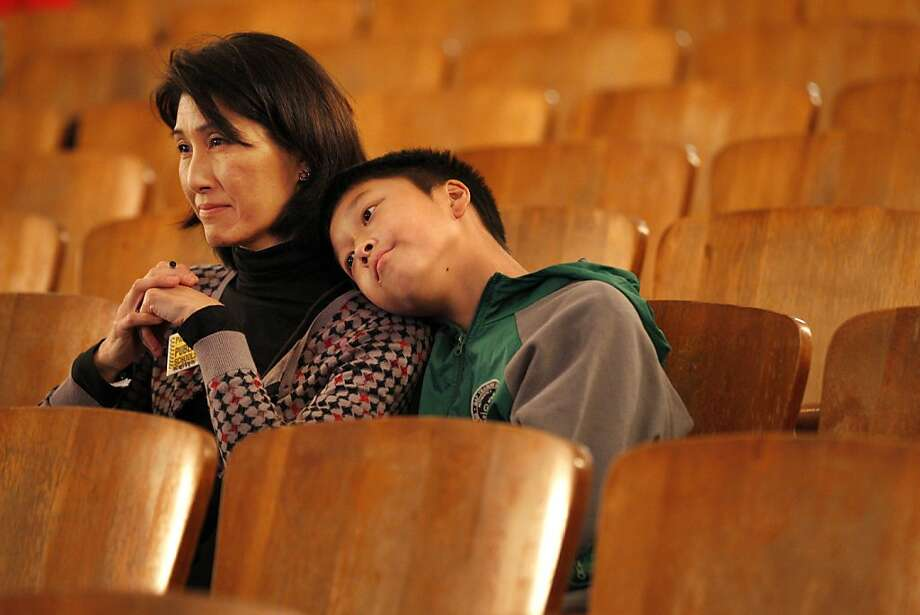 "Kellyn Dong listens with her son Lucas, 11, during ""Stand Up, Don't Stand By: How to Put an End to Bullying in a 24/7 Digital World,"" a presentation on cyberbullying at James Lick Middle School in San Francisco. Photo: Leah Millis, The Chronicle"