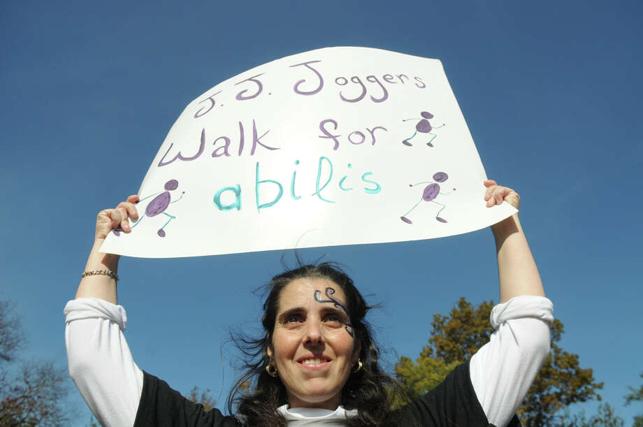 "Jennifer Jaboulay holds her team sign ""JJ Joggers"" as she and hundreds of people turned out for the 2013 Walk in the Park for Abilis at Greenwich Point in Greenwich, Conn., Oct. 27, 2013. Abilis, formerly ARC of Greenwich, has been serving people with developmental disabilities in lower Fairfield County since 1951. The annual walk brings people and families who are supported by Abilis together for a community-wide event aimed at raising funding and awareness for those served by the organization. Senator Richard Blumenthal and First Selectman Peter Tesei were both on hand. Photo: Contributed / Stamford Advocate Freelance"