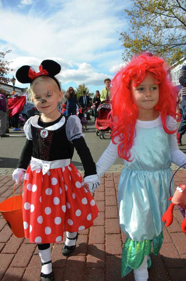 Twin sisters Matilda and Charlotte Doak walk the New Canaan Chamber of Commerce's 32nd Annual Halloween Parade on Sunday, Oct. 27, 2013. Photo: Jeanna Petersen Shepard / New Canaan News Freelance