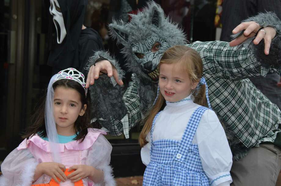 The big bad wolf, Matt Dennebaum, sneaks up behind his daughter, Soleil Dennebaum (in pink) and Reagan Amundsen, at the New Canaan Chamber of Commerce's 32nd Annual Halloween Parade on Sunday, Oct. 27, 2013. Photo: Jeanna Petersen Shepard / New Canaan News Freelance