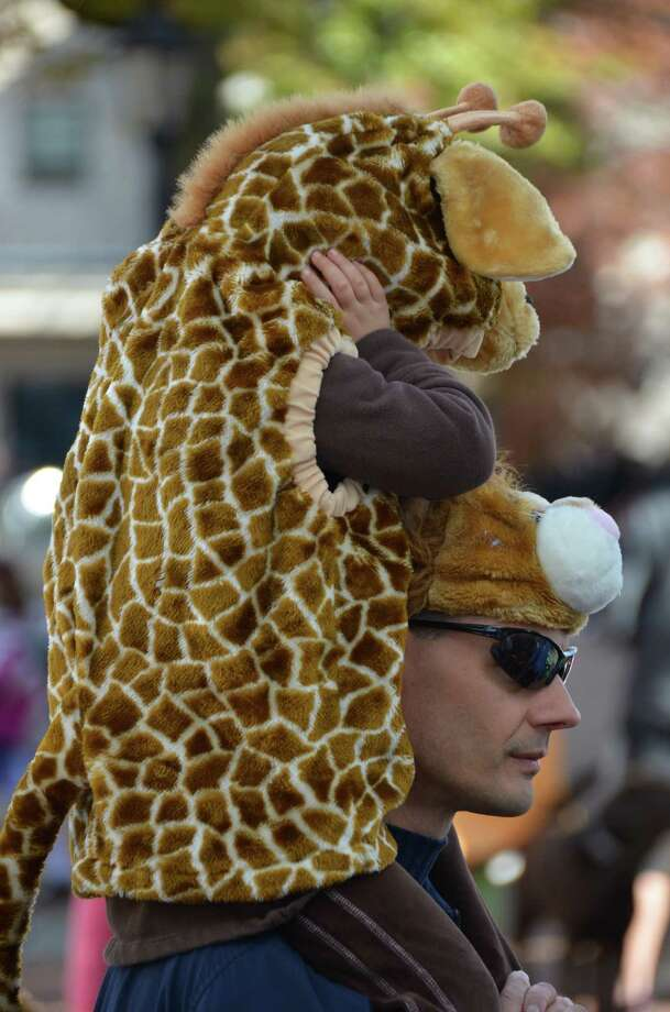 Bruce Colthup carries his little giraffe, Tatum, during the New Canaan Chamber of Commerce's 32nd Annual Halloween Parade on Sunday, Oct. 27, 2013. Photo: Jeanna Petersen Shepard / New Canaan News Freelance