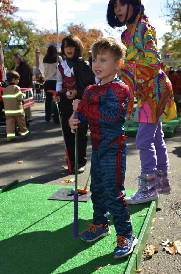 Spiderman Thai Carson plays a little mini golf at the New Canaan Chamber of Commerce's 32nd Annual Halloween Parade on Sunday, Oct. 27, 2013. Photo: Jeanna Petersen Shepard / New Canaan News Freelance