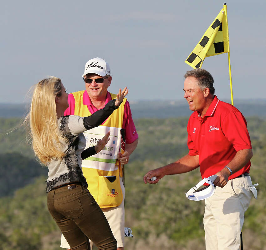 Lindsey Kennemer (left) runs to her father Kenny Perry (right) as Perry's caddie Fred Sanders (center) looks on after Perry won a one-hole sudden-death playoff against Bernhard Langer to win the 2013 AT&T Championship Sunday Oct. 27, 2013 on the AT&T Canyons Course at TPC San Antonio.