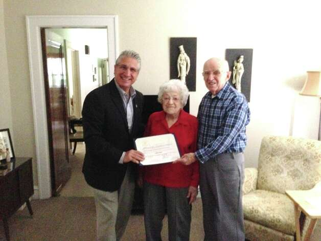 Assemblyman Jim Tedisco presents an Assembly citation to Adeline Morrett on her 100th birthday this month, as her neighbor James A. Wilson of Schenectady watches. She was born Adeline Santabarbara in Mechanicville on Oct. 22, 1913, and has lived in her home on Twelfth Street in Schenectady for 80 years. Morrett told Tedisco that each night at 10 p.m. she calls her two sisters to wish them a good night and toasts a shot of sambuca to good health. (Submitted photo)
