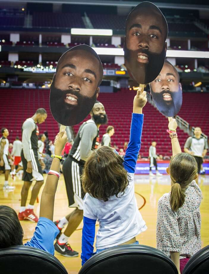 James Harden smiles as he passes a group of young fans holding up his photo during the Houston Rockets Annual Open Practice at Toyota Center on Sunday, Oct. 27, 2013. Photo: Smiley N. Pool, Houston Chronicle