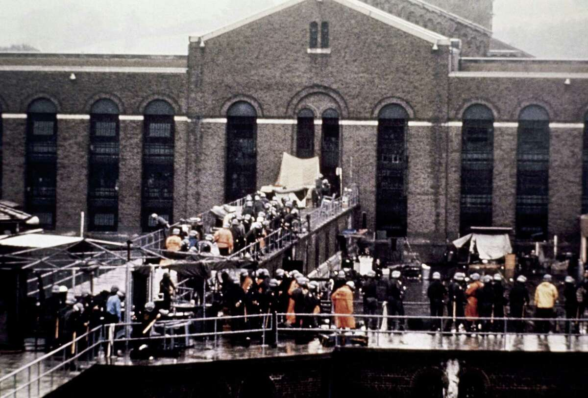 In this Sept. 13, 1971 file photo, prison guards and New York State troopers gather outside Attica State Prison after retaking it from inmates who rioted and held the prison for five days, in Attica, N.Y. New York's Attorney General Eric Schneiderman has asked a state judge to unseal documents about the 1971 riot and retaking of Attica state prison in the nation's bloodiest prison rebellion.