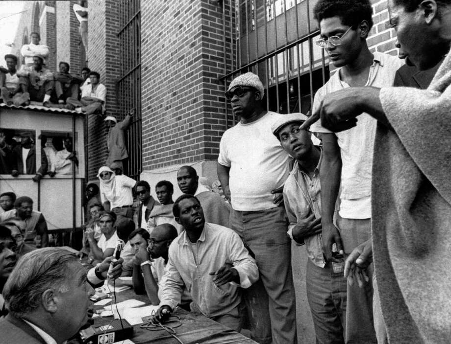 In this file photo of Sept. 10, 1971, inmates of Attica state prison, right, negotiate with state prisons Commissioner Russell Oswald, lower left, at the facility in Attica, N.Y., where inmates had taken control of the maximum-security prison in rural western New York. New York's Attorney General Eric Schneiderman has asked a state judge to unseal documents about the 1971 riot and retaking of Attica state prison in the nation's bloodiest prison rebellion. Photo: Uncredited, AP / AP