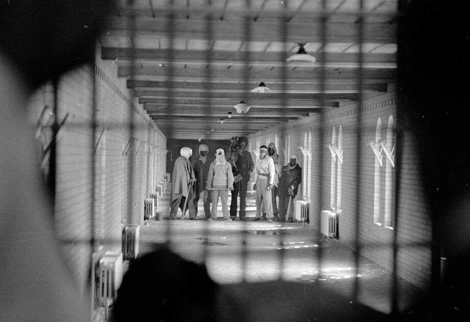 In this Sept. 10, 1971 file photo, inmates wearing cloaks and football helmets stand behind bars in a corridor leading to D block as they begin negotiatiations with New York State officials after a prison uprising at Attica State Prison, in Attica, N.Y. New York�s Attorney General Eric Schneiderman has asked a state judge to unseal documents about the 1971 riot and retaking of Attica state prison in the nation's bloodiest prison rebellion. Photo: Bob Schutz, AP / AP