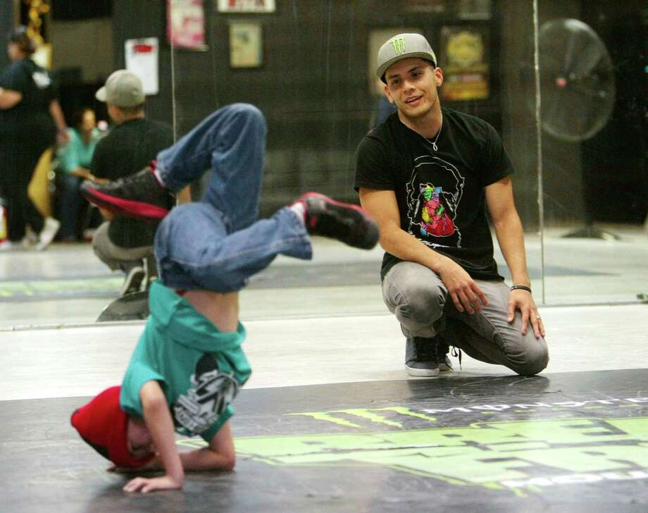 "Jacob Chacon attempts a break-dance move under the watchful eye of Moises ""Moy"" Rivas. Photo: Billy Smith II, Staff / Houston Chronicle"
