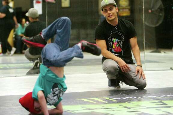 "Jacob Chacon attempts a break-dance move under the watchful eye of Moises ""Moy"" Rivas."