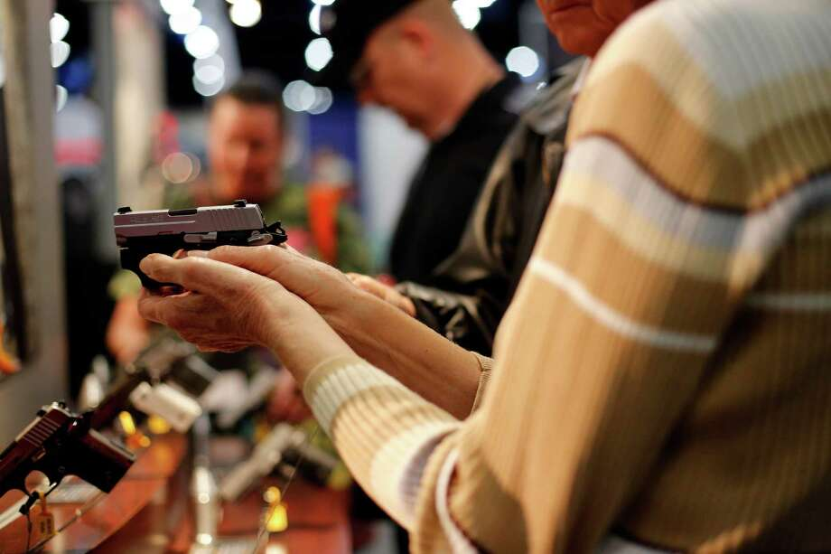 An expo attendee inspects a Sig Sauer pistol, during day 1 of the 142nd NRA annual meetings and exhibits, Friday, May 3, 2013 at the George R Brown convention center in  (TODD SPOTH FOR THE CHRONICLE) Photo: Â TODD SPOTH,  2013 / © TODD SPOTH, 2013