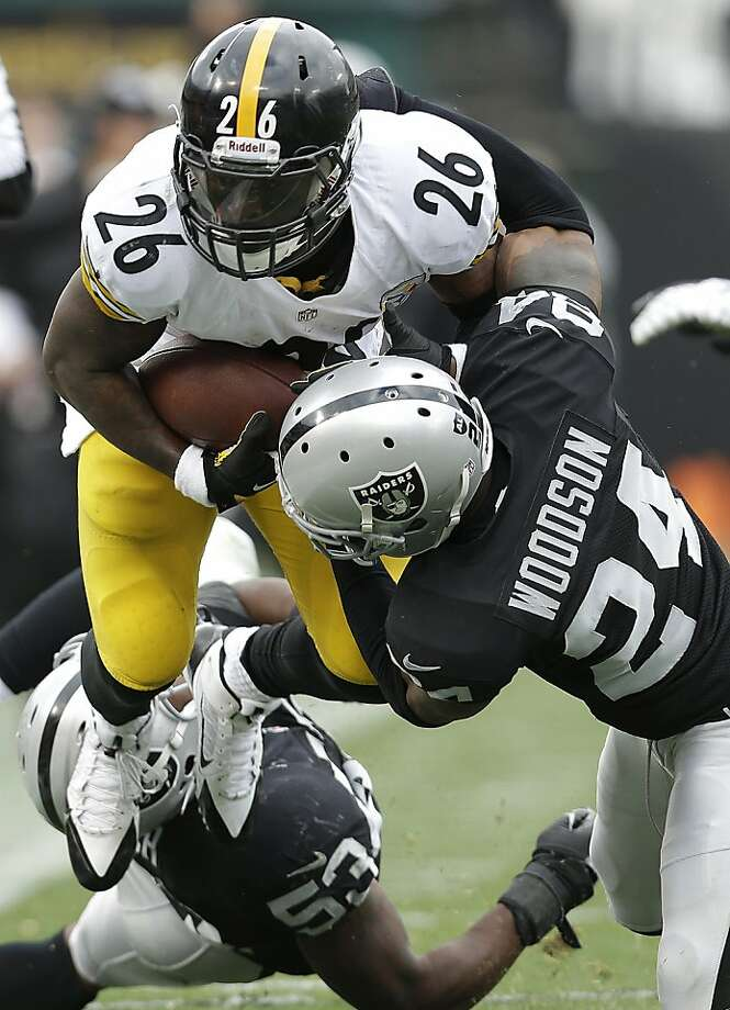 Pittsburgh Steelers running back Le'Veon Bell (26) is tackled by Oakland Raiders cornerback Charles Woodson (24) and linebacker Nick Roach (53) during the third quarter of an NFL football game in Oakland, Calif., Sunday, Oct. 27, 2013. (AP Photo/Marcio Jose Sanchez) Photo: Marcio Jose Sanchez, Associated Press