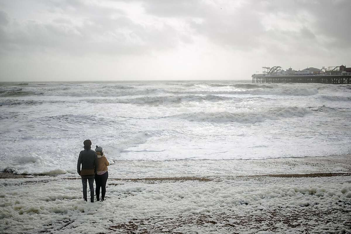 BRIGHTON, UNITED KINGDOM - OCTOBER 27: Members of the public brace the stormy weather conditions on October 27, 2013 in Brighton, UK. Millions of people in parts of the UK have been told to brace themselves for what is predicted to be one of the worst storms for years with heavy rain and hurricane-force winds expected tonight and tomorrow morning as the storm hits the South West then moves north and eastwards. (Photo by Dan Dennison/Getty Images) *** BESTPIX ***