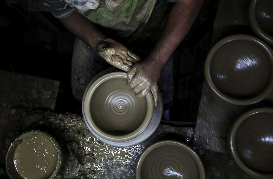 A Palestinian man, uses a pottery wheel to construct a clay vessel, at the oldest pottery workshop in Gaza City, Sunday, Oct. 27, 2013. Pottery is an ancient and traditional craft in Gaza. Local workshops usually produce products such as bowls, pitchers, flower pots, and vases, including a big black pottery vessel known as 'al-Qedra' that is used for cooking a traditional Gazan meal made out of rice, meat, garlic and onions. (AP Photo/Hatem Moussa) Photo: Hatem Moussa, Associated Press