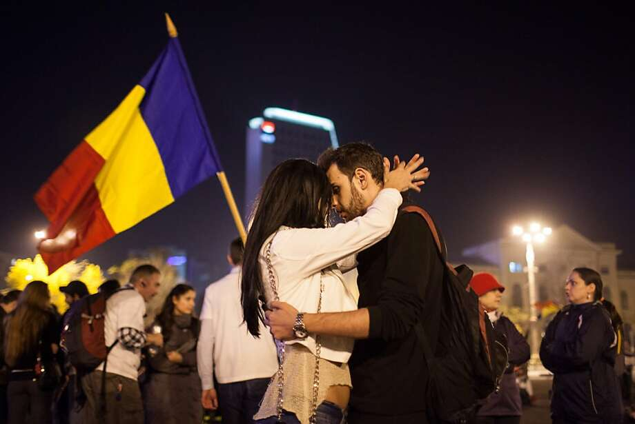 Two protesters share a moment of intimacy outside the Romanian government headquarters during a rally in Bucharest against the Rosia Montana Gold Corporation (RMGC), a Canadian gold mine project using cyanide, and against shale gas exploitation, on October 27, 2013, in Bucharest, Romania. Some 2500 people took to the streets of Bucharest to protest plans by a Canadian company to open Europe's largest goldmine in a Transylvanian village and the exploration of shale gas by US oil giant Chevron.     TOPSHOTS/AFP PHOTO/ANDREI PUNGOVSCHIANDREI PUNGOVSCHI/AFP/Getty Images Photo: Andrei Pungovschi, AFP/Getty Images