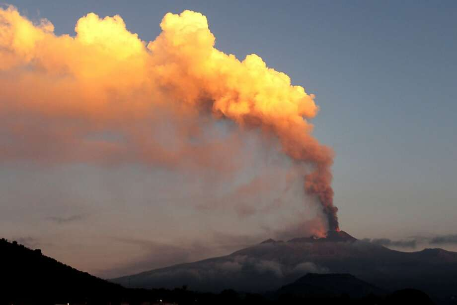 Smoke billows during an eruption of Mount Etna volcano as seen from the village of Viagrande, near the Sicilian town of Catania, Italy, Saturday, Oct. 26, 2013. Mount Etna, Europe's most active volcano, has erupted, sending up a towering plume of ash visible in much of eastern Sicily. Etna's eruptions are not infrequent, although the last major one occurred in 1992. Catania airport said the eruption Saturday forced closure of nearby air space before dawn, but authorities lifted the closure in early morning. Several inhabited villages dot the mountain's slopes, but evacuations weren't necessary despite the lava flow. (AP Photo/Carmelo Imbesi) Photo: Carmelo Imbesi, Associated Press
