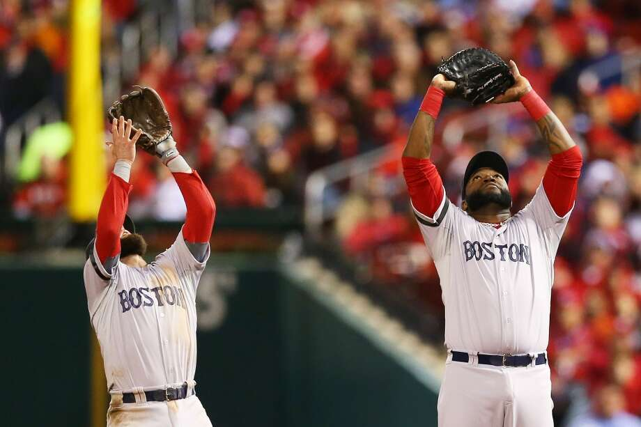 Dustin Pedroia #15 and David Ortiz #34 of the Red Sox look to catch a ball. Photo: Ronald Martinez, Getty Images