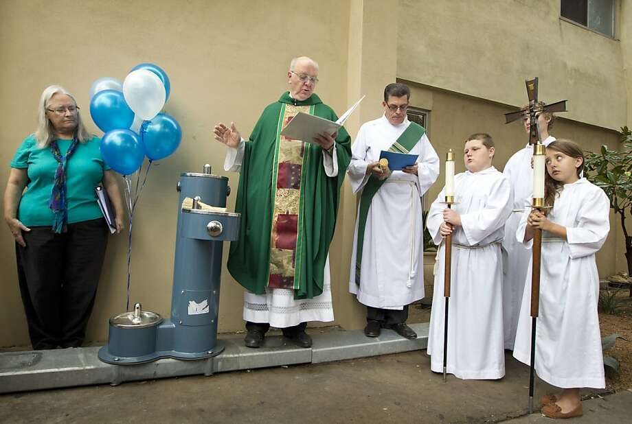 May its flowing waters refresh the thirsty, both human and canine: The Rev. Charles Kullmann blesses a new public 