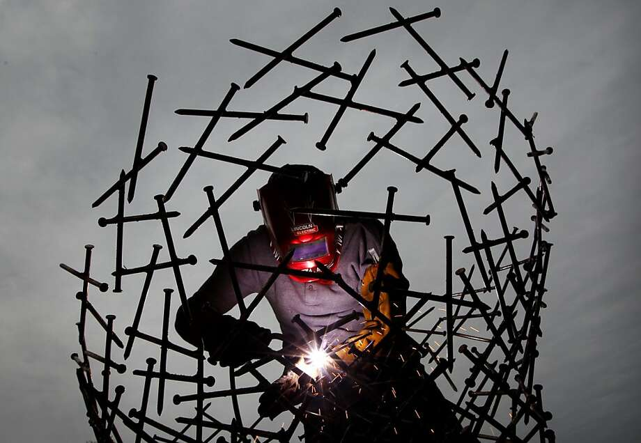 Wait up, judges, I'm almost done!Sculptor Elisha Gold creates a giant head out of 6-inch nails on the final day of the RiverArtsFest juried art show in Memphis. Photo: Jim Weber, Associated Press