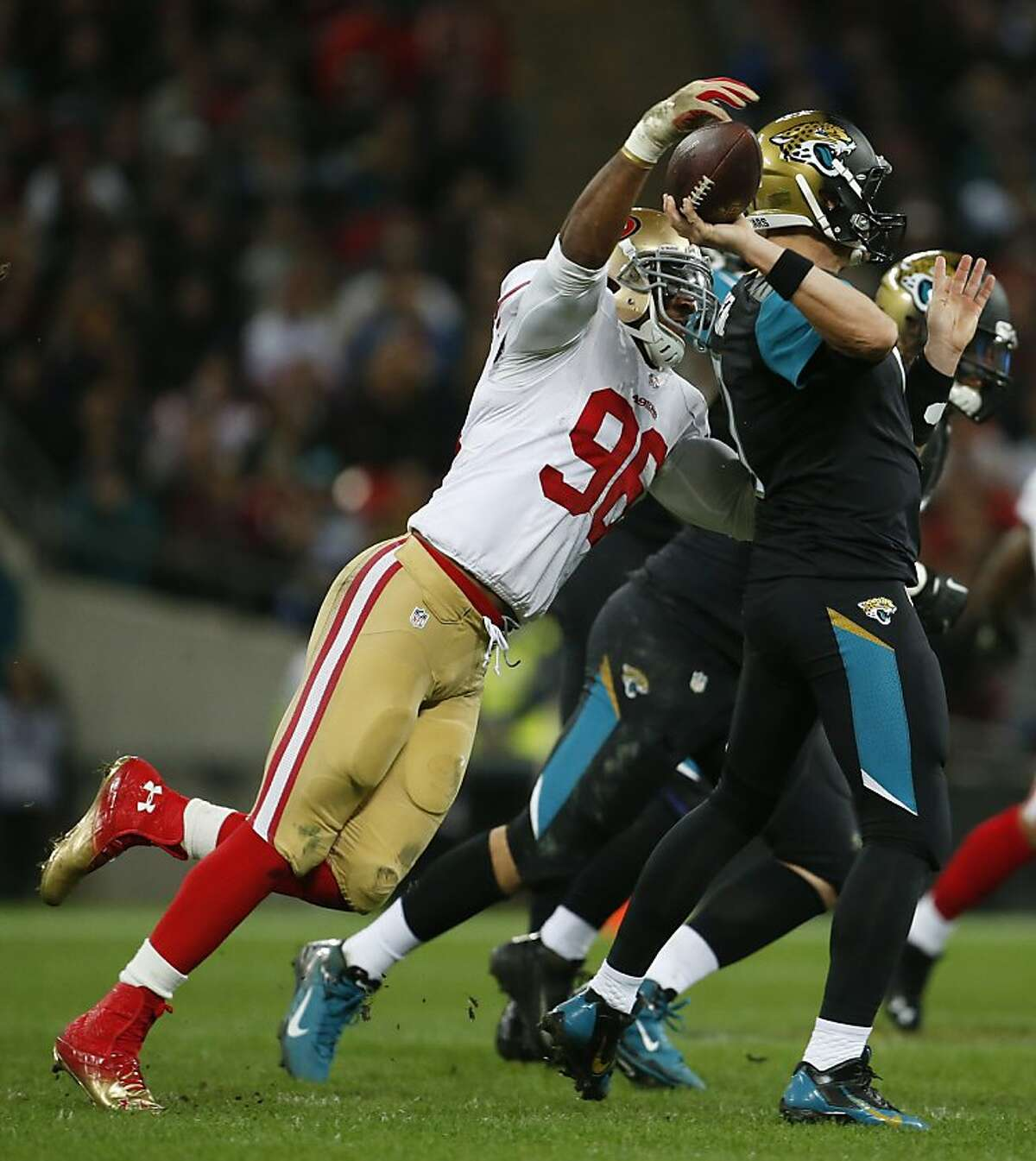 San Francisco 49ers linebacker Corey Lemonier (96) tries to knock the ball out of Jacksonville Jaguars quarterback Chad Henne's hand during the first half of an NFL football game at Wembley Stadium, London, Sunday, Oct. 27, 2013.