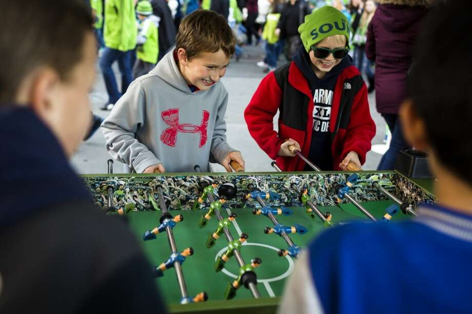 Young boys play Sounders FC-themed foosball outside of the stadium before the final game of the regular season against the LA Galaxy on Sunday. (Jordan Stead, seattlepi.com) Photo: JORDAN STEAD, SEATTLEPI.COM