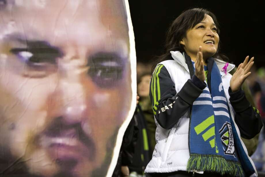 """Abreast of a gigantic Dempsey """"Deuce Face,"""" a fan enjoys the first half of a Sounders game against the LA Galaxy on Sunday. the game ended in a 1-1 tie.(Jordan Stead, seattlepi.com) Photo: JORDAN STEAD, SEATTLEPI.COM"""