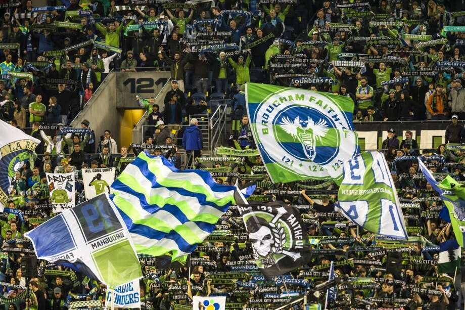 Sounders FC fans hoist flags during the first half of a game Sunday. The game ended in a 1-1 tie. (Jordan Stead, seattlepi.com) Photo: JORDAN STEAD, SEATTLEPI.COM