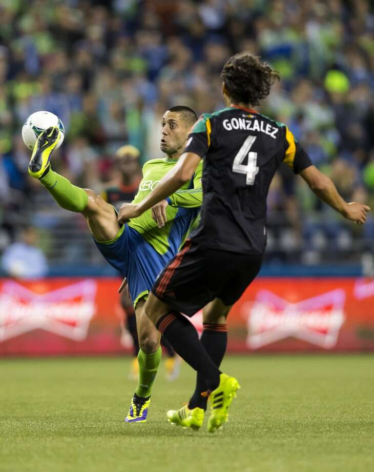 Clint Dempsey, left, attempts to clear the ball away during the first half of Sunday. (Jordan Stead, seattlepi.com) Photo: JORDAN STEAD, SEATTLEPI.COM