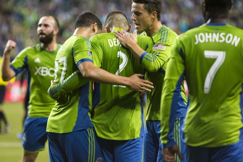 Clint Dempsey, center, is congratulated by teammates after making his first goal as a Sounders player Sunday. (Jordan Stead, seattlepi.com) Photo: JORDAN STEAD, SEATTLEPI.COM