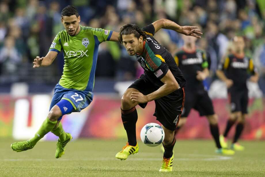 Lamar Neagle, left, and Omar Gonzales, right, compete for ball control Sunday. (Jordan Stead, seattlepi.com) Photo: JORDAN STEAD, SEATTLEPI.COM