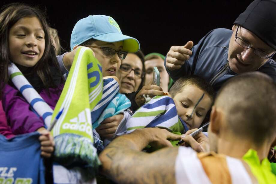 Clint Dempsey, bottom right, signs autographs for fans following a game against the LA Galaxy on Sunday.(Jordan Stead, seattlepi.com) Photo: JORDAN STEAD, SEATTLEPI.COM
