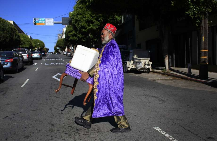 Carrying a thrown that used to be his grandmother's chair, King Kobbler crosses Bryant Street where he hopes to set up camp in front of captive commuter audience trying to get on the Bay Bridge during a BART Strike in San Francisco, Calif. Photo: Mike Kepka, The Chronicle