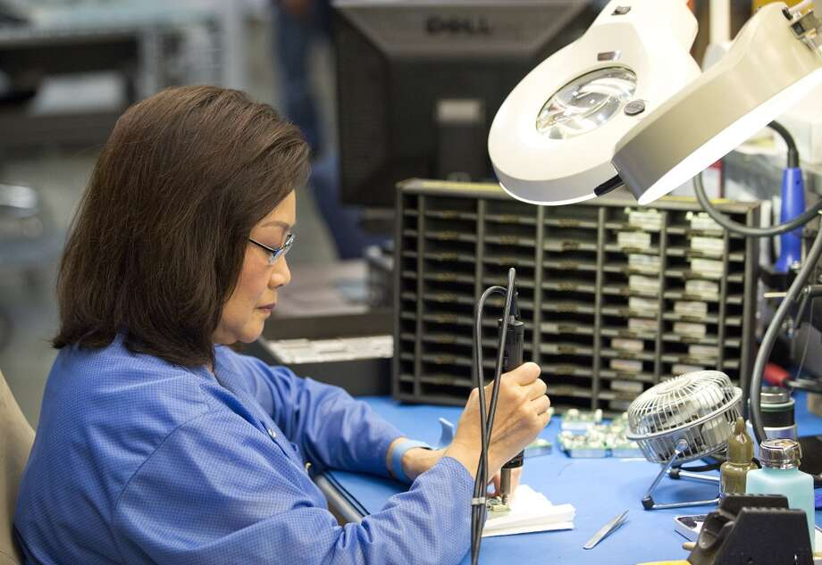 Anh Quach solders and cleans computer chips that will be used in seismic equipment being manufactured at Fairfield Nodal's facility in Sugar Land, Texas. The equipment is used by oil companies to scan for oil fields under the ocean floor. Photo: Thomas B. Shea, For The Chronicle