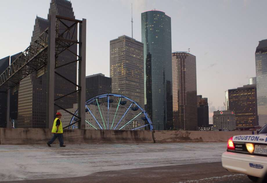 Crews scramble to clean up shattered glass after a big-rig crashed and lost its load before dawn Monday on Interstate 45 downtown. Photo: Johnny Hanson, Houston Chronicle