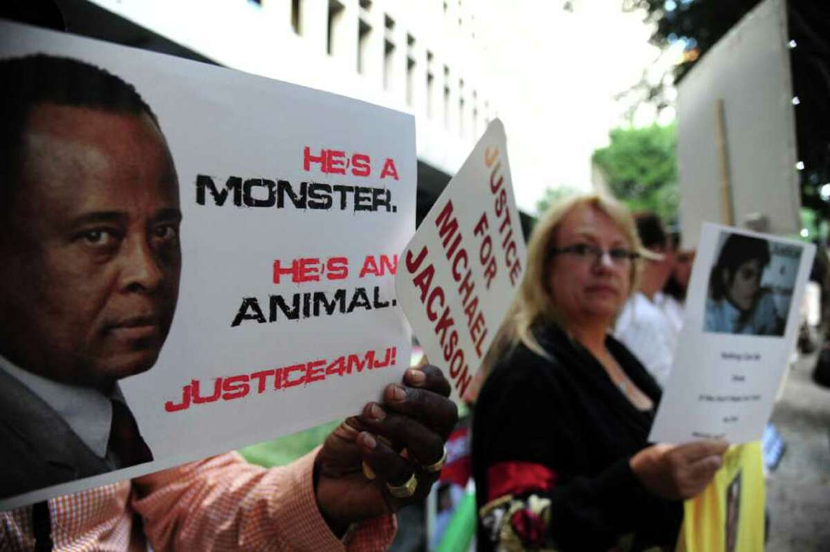 Supporters at the late pop star Michael Jackson hold signs outside Los Angeles Superior Court where opening statements will be heard in the involuntary manslaughter trial of Jackson's personal physian Dr Conrad Murray September 27, 2011.