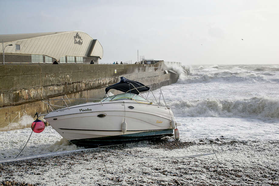 A boat is washed ashore on Brighton beach amid stormy conditions on October 27, 2013 in Brighton, UK. Millions of people in parts of the UK have been told to brace themselves for what is predicted to be one of the worst storms for years with heavy rain and hurricane-force winds expected tonight and tomorrow morning as the storm hits the South West then moves north and eastwards. Photo: Dan Dennison, Getty Images / 2013 Getty Images