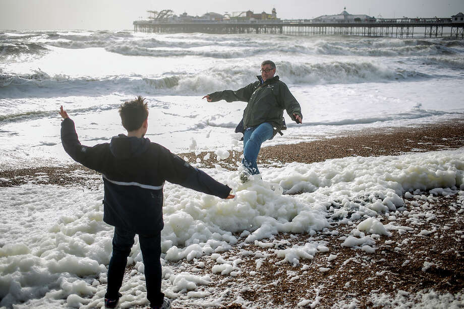 Father and son play on Brighton beach in stormy conditions on October 27, 2013 in Brighton, UK. Millions of people in parts of the UK have been told to brace themselves for what is predicted to be one of the worst storms for years with heavy rain and hurricane-force winds expected tonight and tomorrow morning as the storm hits the South West then moves north and eastwards. Photo: Dan Dennison, Getty Images / 2013 Getty Images