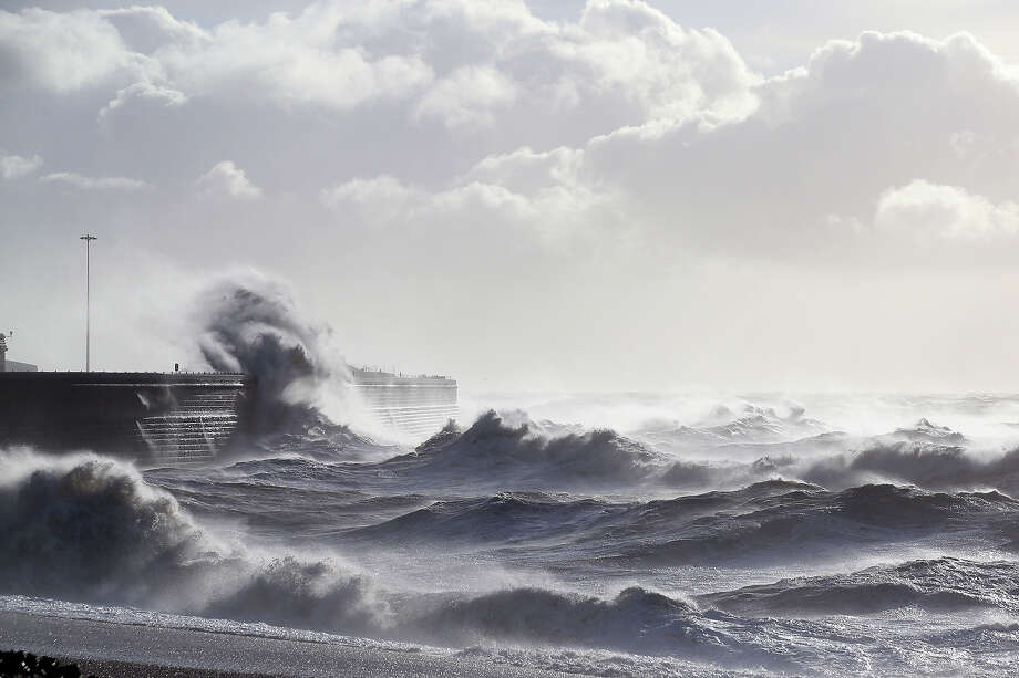 Large waves, produced by storm force winds, break against the harbour wall on October 28, 2013 in Dover, England.  Approximately 220,000 homes are without power and two deaths have been recorded after much of southern England has been affected by a severe storm. Transport links on road, rail, air and sea have been severely disrupted by hurricane-force winds  that have almost reached 100 mph in places. Photo: Oli Scarff, Getty Images / 2013 Getty Images