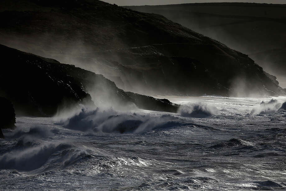 Large waves, produced by storm force winds, break along the coast at Porthleven on October 28, 2013 in Cornwall, England. Approximately 220,000 homes are without power and two deaths have been recorded after much of southern England has been affected by a severe storm. Transport links on road, rail, air and sea have been severely disrupted by hurricane-force winds that have almost reached 100 mph in places. Photo: Matt Cardy, Getty Images / 2013 Getty Images