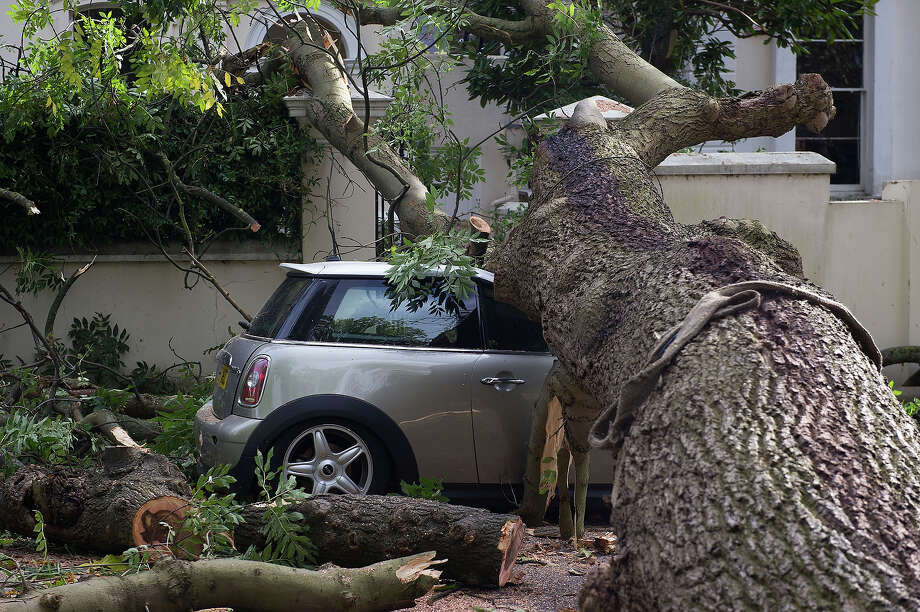A car crushed by a fallen tree, following an overnight storm across southern England, in Camden Square on October 28, 2013 in London, England. Approximately 220,000 homes are without power and two deaths have been recorded after much of southern England has been affected by a severe storm. Transport links on road, rail, air and sea have been severely disrupted by hurricane-force winds that have almost reached 100 mph in places. Photo: Zak Hussein, Getty Images / 2013 Zak Hussein