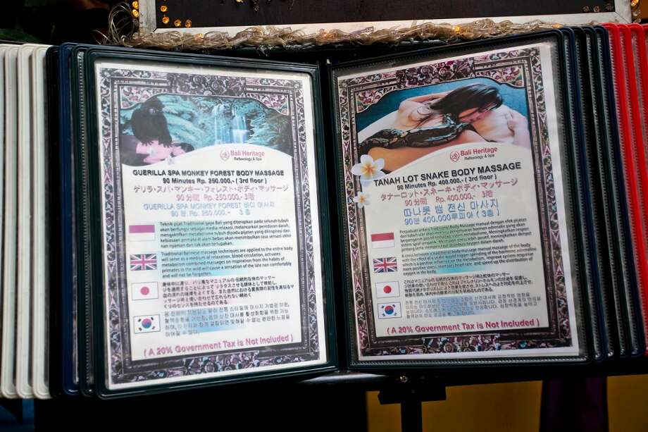 A list of treatments is displayed in front of the Bali Heritage Reflexology and Spa on October 27, 2013 in Jakarta, Indonesia. The snake spa offers a unique massage treatment which involves having several pythons placed on the customers body. The movement of the snakes and the adrenaline triggered by fear is said to have a positive impact on the customers metabolism. Photo: Getty Images