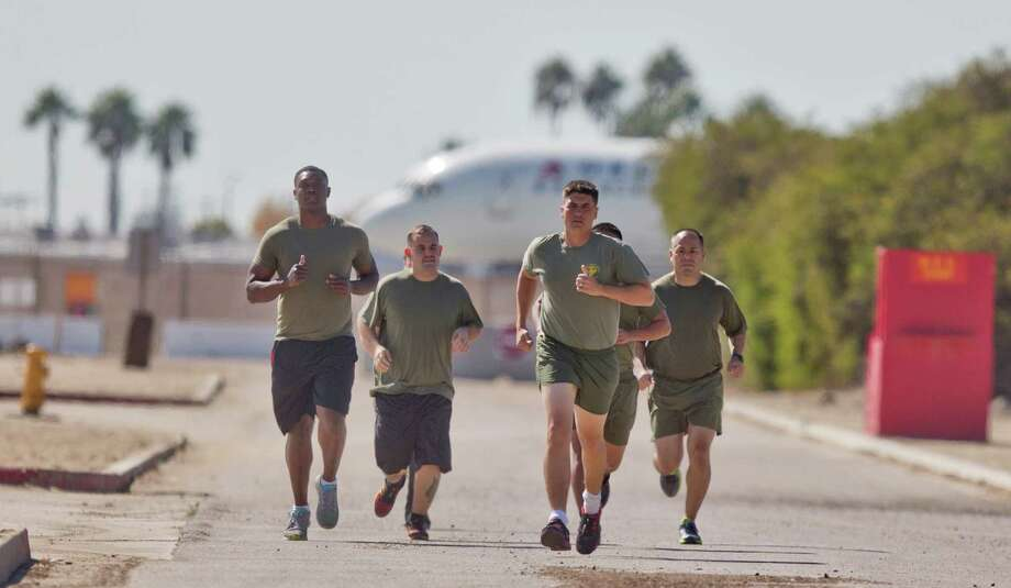 "In a Thursday, Oct. 17, 2013 photo, a group of sailors and Marines who failed the so-called ""tape test'' are led by an instructor on a three mile run as they work to improve their fitness and remain in the military, at the Marine Corps Recruit Depot in San Diego. Doctors say a number of military personnel are turning to liposuction to remove excess fat from around the waist so they can pass the Pentagon's body fat test. Some service members say they have no other choice because the Defense Department's method of estimating body fat is weeding out not just flabby physiques but bulkier, muscular builds. A number of fitness experts and doctors agree, and they're calling for the military's fitness standards to be revamped. Photo: Lenny Ignelzi, AP / AP"
