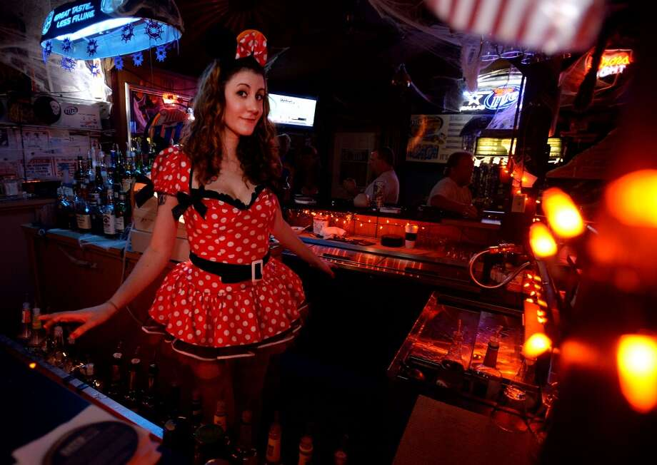 Dressed as Minnie Mouse, Rebekah Herzberg tends bar at King Arthur's Pub in Beaumont on Monday. Herzberg and other bar staff will be sporting costumes through out the month. Photo taken Monday, October 14, 2013 Guiseppe Barranco/The Enterprise