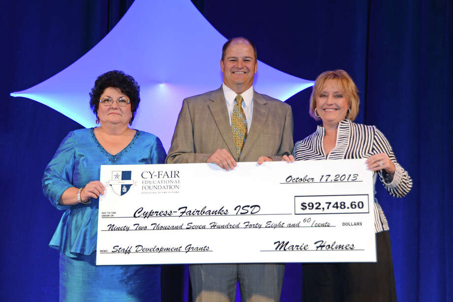 Salute to the Stars Gala co-chairs Darlene Hajduk, left, and Lauri Baker present CFISD Superintendent Mark Henry with a check worth $92,748.60 for Cy-Fair Educational Foundation staff development grants raised from the 2012 Salute to the Stars and Cypress Photo: Cy-Fair Educational Foundation