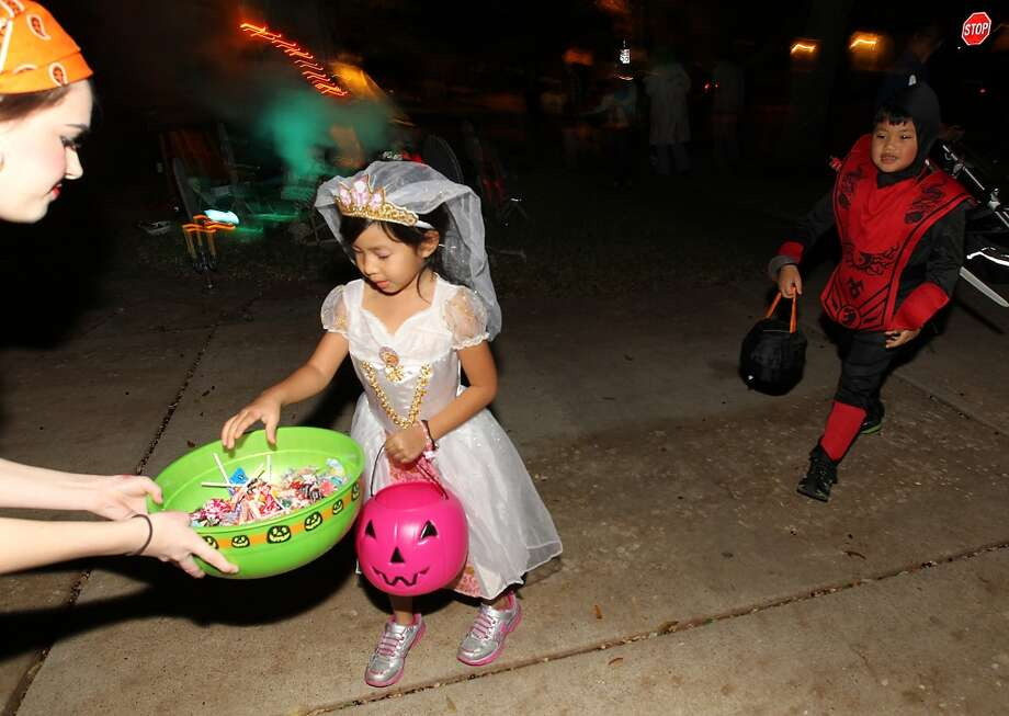 Sofia Ho, 5, gets candy from Nicole Dorsey as she goes trick-or-treating in the New Territory subdivision on Halloween night. Photo: Karen Warren, Houston Chronicle