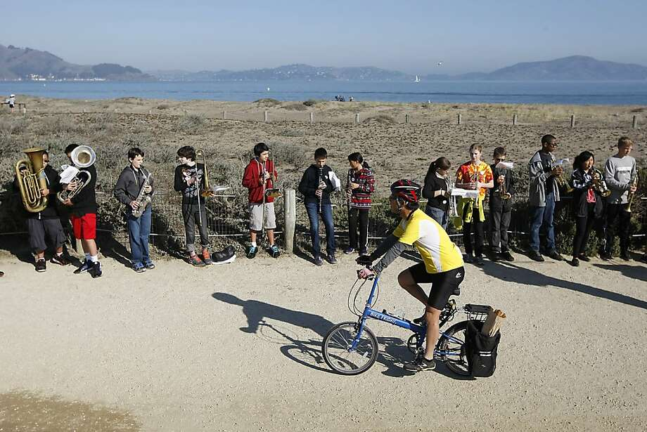"A cyclist passes the Presidio Middle School band during the ""Crissy Broadcast"" at Crissy Field in S.F., a large public art project over the weekend. Photo: Michael Short, The Chronicle"