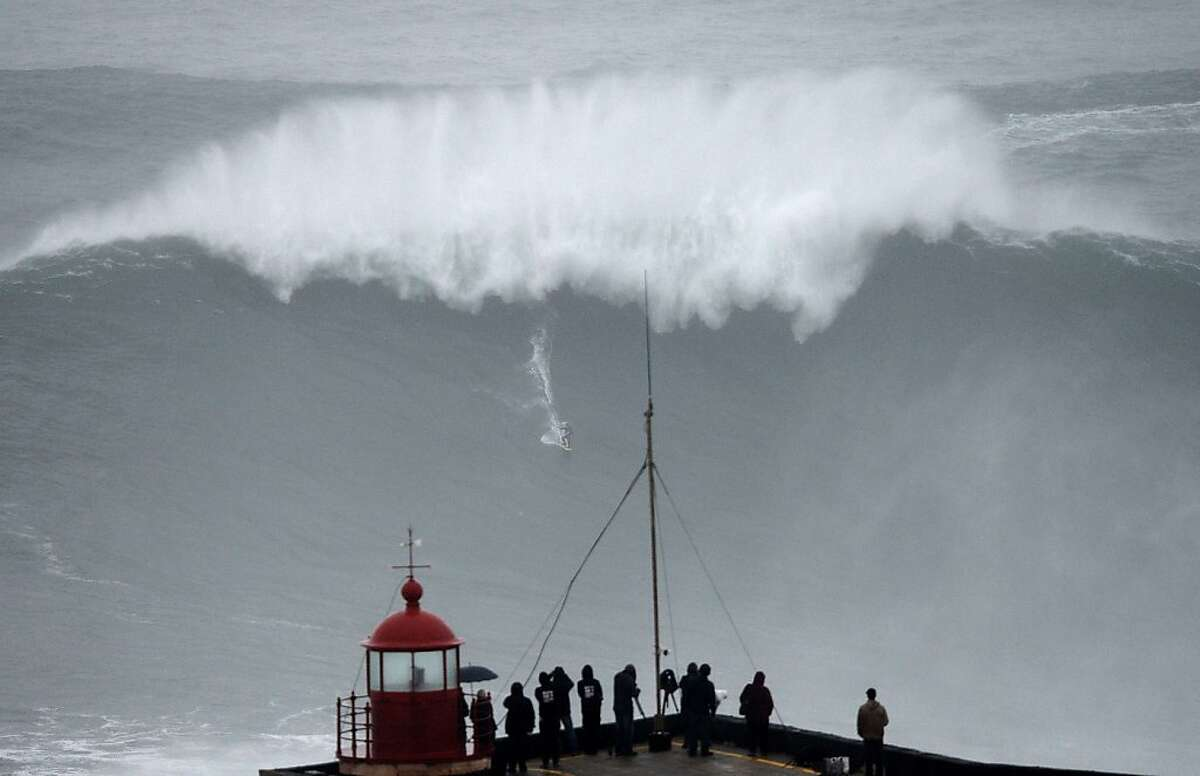 We see your Mavericks, California, and raise you one Nazare: Brazilian big wave surfer Carlos Burle rides a ridiculously large wave in Nazare, Portugal.